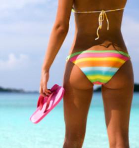 woman holding pink flip flops on a tropical beach